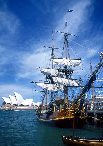 stock photo image: Australia, New South Wales, Sydney, Sydney Harbour, Sydney Harbor, Sydney Opera House, Architecture, Joern Utzon, opera house, bounty, hms bounty, the bounty, cloud, clouds, sky, skies, sky scenes, ship, ships, sailing ship, sailing ships, early sailing ship, early sailing ships.